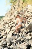 男孩上升的岩石小山 免版税库存照片
