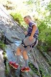 男孩上升的岩石 库存照片