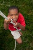 男孩上升的绳索 免版税库存照片