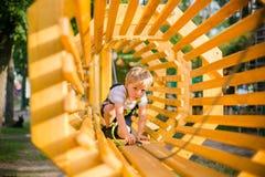 男孩上升的通行证障碍在绳索公园 库存图片