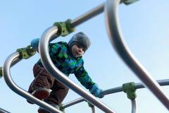 男孩上升的金属桥梁 免版税库存照片