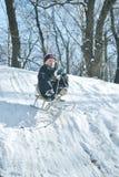 男孩下来去雪撬 免版税库存图片
