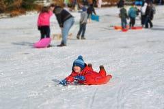男孩下滑多雪的冬天年轻人的乐趣小山 免版税库存照片