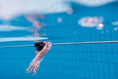 在游泳场的男孩下潜 免版税库存图片