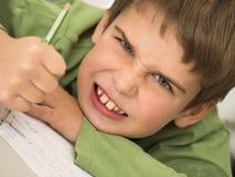 男孩不喜欢执行家庭作业 库存图片