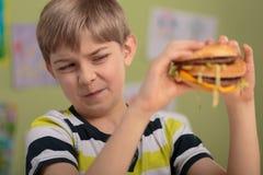 男孩不喜欢汉堡包 免版税图库摄影