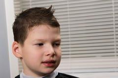 男孩与发型和与容易梳的应用的代理,坐头发 库存图片