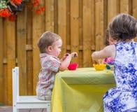 男孩与孩子一起坐洗染的复活节彩蛋 库存图片