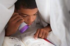 男孩与火炬的阅读书在鸭绒垫子下 免版税图库摄影