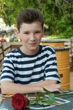 男孩与起来了在街道咖啡馆的一张桌上 免版税图库摄影