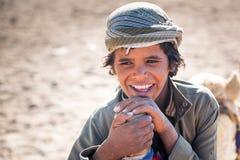 男孩与骆驼一起使用在沙漠的流浪的村庄 免版税库存图片