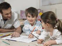 男孩与说谎在地板上的姐妹和父亲的彩图 库存图片