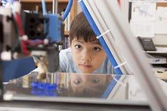男孩专心地观看机器 免版税库存照片