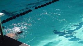 男孩严谨地在接踵而来的体育运动游泳竞赛的仰泳被训练 活动公共 股票录像