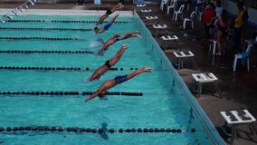 男孩严谨地在接踵而来的运动游泳竞赛的适当的体育潜水被训练 活动公共 股票视频