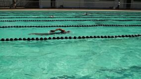 男孩严谨地在接踵而来的运动游泳竞赛的sidestroke被训练 活动公共 股票录像