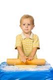 男孩为做蛋糕用手揉面团 图库摄影