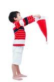 男孩举行向上看圣诞老人的帽子 免版税库存照片