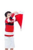 男孩举行在白色背景的圣诞老人帽子 免版税库存图片