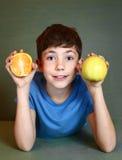 男孩举行桔子和苹果接近的画象 免版税库存图片