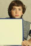 男孩举行白纸长方形框架 免版税图库摄影