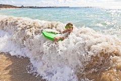 男孩乐趣有冲浪板 库存图片