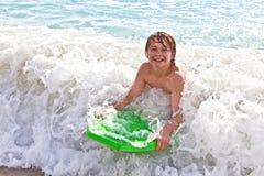 男孩乐趣有冲浪板 免版税库存照片