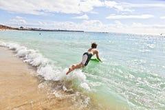 男孩乐趣有冲浪板 免版税图库摄影
