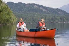 男孩乘独木舟的女孩 免版税图库摄影