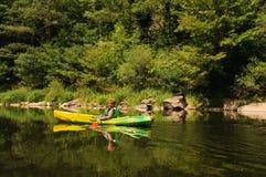 男孩乘独木舟的河 库存图片