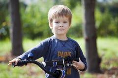 男孩乘驾一辆自行车在城市公园 免版税库存图片