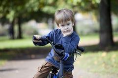男孩乘驾一辆自行车在城市公园 免版税库存照片