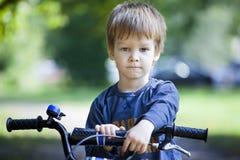 男孩乘驾一辆自行车在城市公园 库存图片