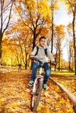 男孩乘驾在秋天公园 库存照片