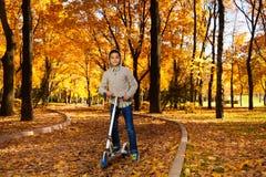 男孩乘驾滑行车在10月公园 免版税图库摄影