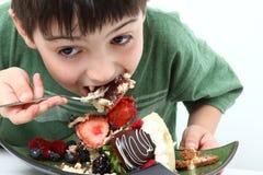男孩乳酪蛋糕吃 免版税图库摄影