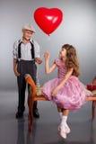 男孩产生一个红色气球女孩 免版税图库摄影