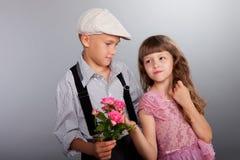男孩产生一朵花女孩 免版税库存图片
