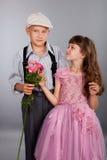 男孩产生一朵花女孩 免版税图库摄影