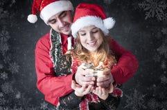 男孩产生圣诞节礼品她的女朋友。 免版税库存照片