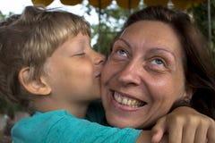 男孩亲吻他的面颊的母亲 有母亲的儿子容忍的 免版税库存照片