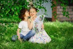 男孩亲吻有爱好者的女孩 免版税库存照片