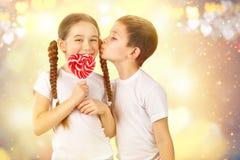 男孩亲吻有糖果红色棒棒糖的小女孩在心脏形状 华伦泰` s天艺术画象 免版税图库摄影