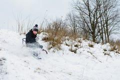 男孩从小山掩藏在雪撬在公园 免版税库存图片
