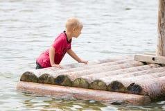 男孩他推进的木筏年轻人 免版税库存图片