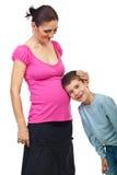 男孩他的听怀孕的母亲肚子 免版税库存图片