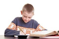 男孩他的家庭作业工作 库存照片