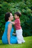 男孩他的拥抱新妈妈老的公园二年 免版税图库摄影