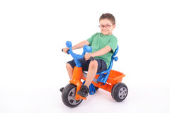 男孩他的骑马三轮车年轻人 库存照片