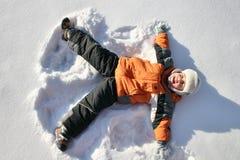 男孩位于雪 免版税库存图片